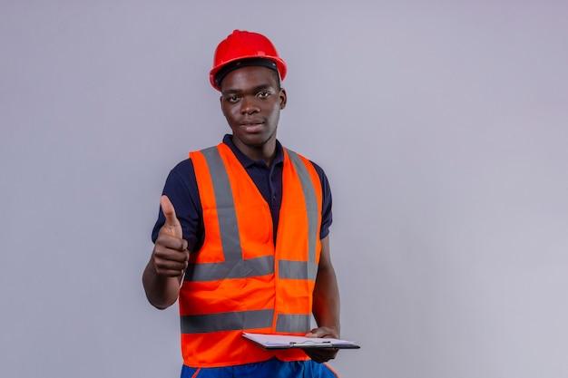 Jeune Homme De Constructeur Afro-américain Portant Un Gilet De Construction Et Un Casque De Sécurité Avec Le Sourire Sur Le Visage Montrant Le Pouce Debout Photo gratuit