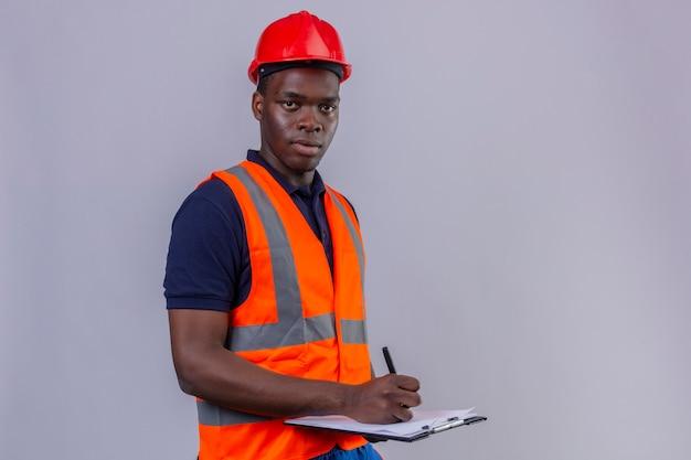 Jeune Homme De Constructeur Afro-américain Portant Un Gilet De Construction Et Un Casque De Sécurité Tenant Le Presse-papiers Et Un Stylo Avec Un Visage Sérieux Debout Photo gratuit