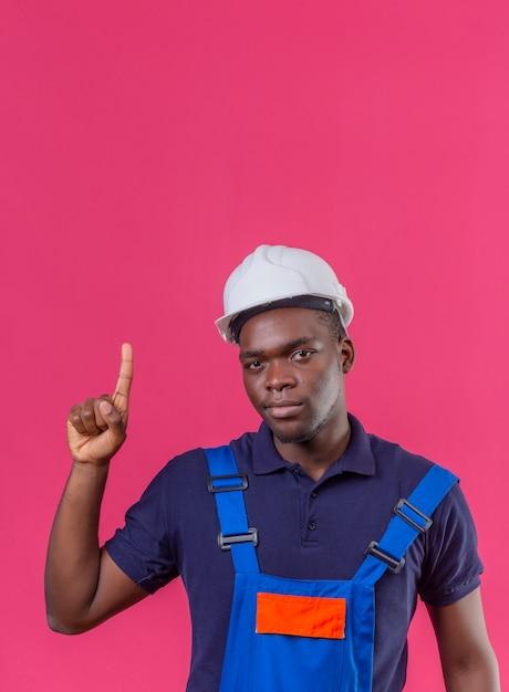 Jeune Homme De Constructeur Afro-américain Portant Des Uniformes De Construction Et Un Casque De Sécurité Debout Avec Le Doigt D'avertissement De Danger Sur Rose Isolé Photo gratuit