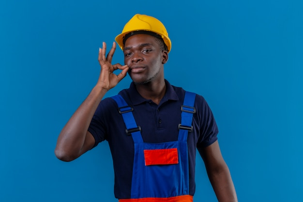 Jeune Homme De Constructeur Afro-américain Portant Des Uniformes De Construction Et Un Casque De Sécurité Faisant Un Geste De Silence Faisant Comme Fermer Sa Bouche Avec Une Fermeture éclair Sur Bleu Isolé Photo gratuit