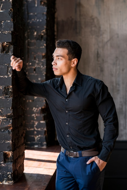 Jeune homme contemplé, la main dans la poche, regardant au loin Photo gratuit