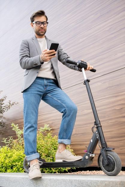 Jeune Homme Contemporain En Smart Casualwear Lecture Message Dans Smartphone En Se Tenant Debout Sur Le Scooter à L'extérieur Photo Premium
