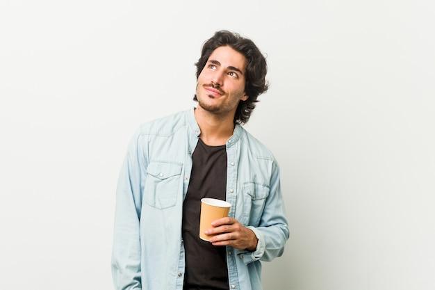 Jeune Homme Cool, Boire Un Café Rêvant D'atteindre Des Objectifs Et Des Fins Photo Premium