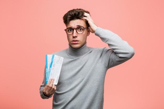Jeune homme cool tenant un billet d'avion étant choqué, elle s'est souvenue d'une réunion importante. Photo Premium
