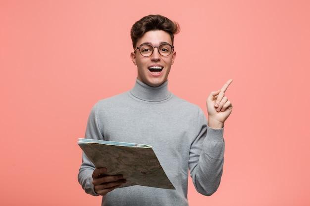 Jeune homme cool tenant une carte pointant du doigt vers vous comme si une invitation se rapprochait. Photo Premium