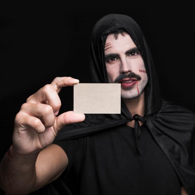 Jeune homme en costume d'halloween noir montrant une petite carte de papier vierge Photo gratuit