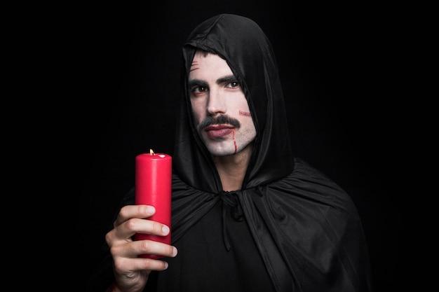Jeune homme en costume d'halloween noir posant en studio avec une bougie Photo gratuit
