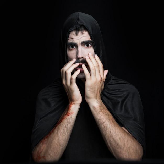 Jeune homme en costume d'halloween noir qui pose en studio Photo gratuit