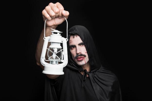 Jeune homme en costume d'halloween posant en studio avec lanterne Photo gratuit