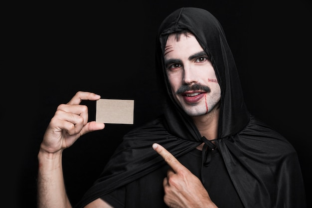 Jeune homme en costume d'halloween posant en studio avec un petit bout de papier Photo gratuit
