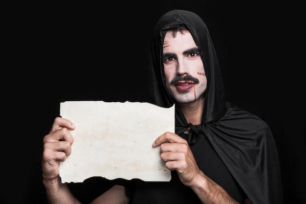 Jeune homme en costume d'halloween qui pose en studio avec une feuille de papier Photo gratuit