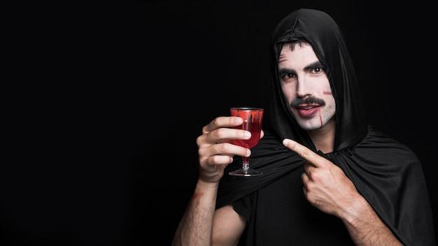 Jeune homme en costume d'halloween tenant un verre à vin Photo gratuit