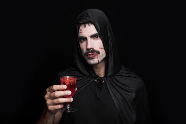Jeune homme en costume noir qui pose en studio avec du verre Photo gratuit