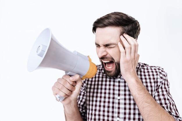 Un jeune homme crie. il a mal a la tete. il se sent très mal Photo Premium