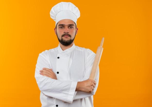 Jeune Homme Cuisinier En Uniforme De Chef Debout Avec Une Posture Fermée Et Tenant Un Rouleau à Pâtisserie Photo gratuit