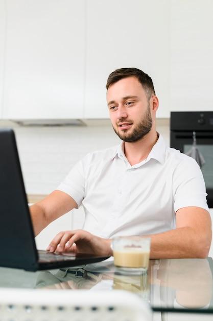 Jeune homme dans la cuisine travaillant sur un ordinateur portable Photo gratuit