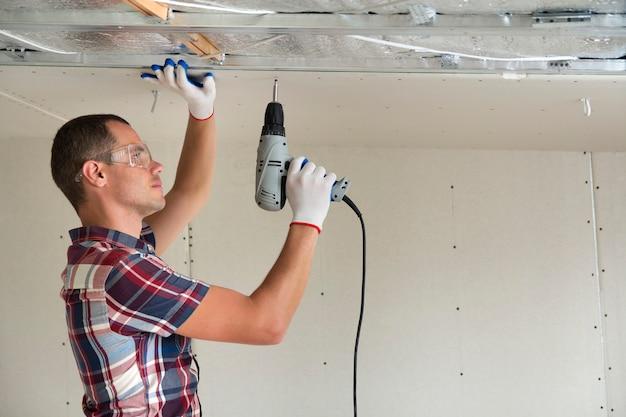 Jeune homme dans la fixation de plafond suspendu de cloison sèche Photo Premium