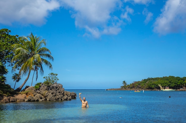 Un Jeune Homme Dans La Mer Des Caraïbes Sur West End Beach Sur L'île De Roatan. Honduras Photo Premium