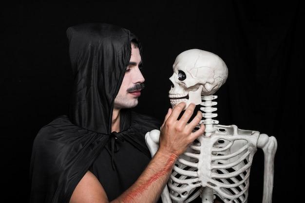 Jeune homme, dans, noir, manteau, à, capuche, regarder, squelette Photo gratuit