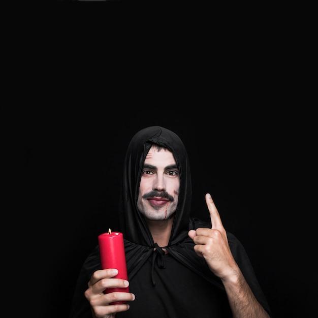 Jeune homme, dans, noir, manteau, debout, dans studio, à, bougie Photo gratuit