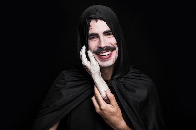 Jeune homme, dans, noir, vêtements, tenue, cadavre, main, sourire Photo gratuit