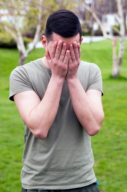 Jeune homme dans un parc public ayant mal à la tête et plein de problèmes, se tenant la tête. Photo Premium
