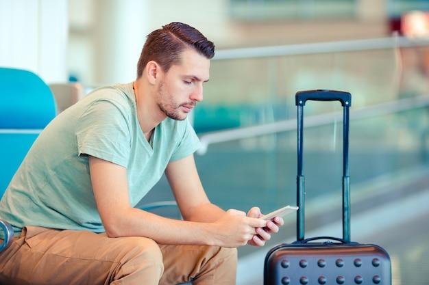 Jeune homme dans un salon d'aéroport en attente d'un avion. Photo Premium