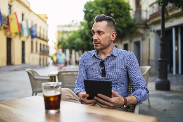Jeune Homme Dans Une Tenue Formelle Assis Dans Un Café En Plein Air Tenant Une Tablette Et Boire Une Boisson Froide Photo gratuit