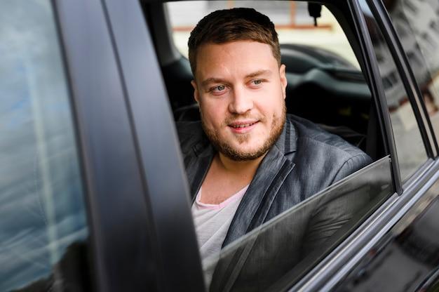Jeune homme dans la voiture avec la fenêtre ouverte Photo gratuit