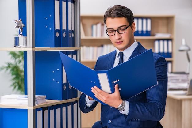 Jeune homme debout à côté de l'étagère avec des dossiers Photo Premium