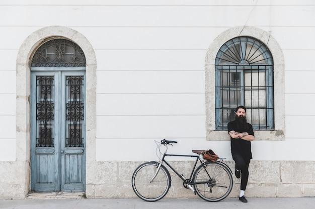 Jeune homme debout devant la fenêtre avec son bras croisé près de sa bicyclette Photo gratuit