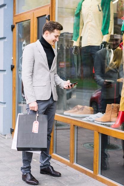 Jeune homme, debout, devant, magasin, utilisation, smartphone Photo gratuit