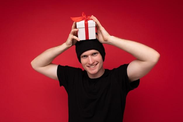 Jeune Homme Debout Isolé Sur Fond Rouge Portant Un Chapeau Noir Et Un T-shirt Noir Tenant Une Boîte Cadeau Blanche Avec Un Ruban Rouge Et Regardant La Caméra. Photo Premium