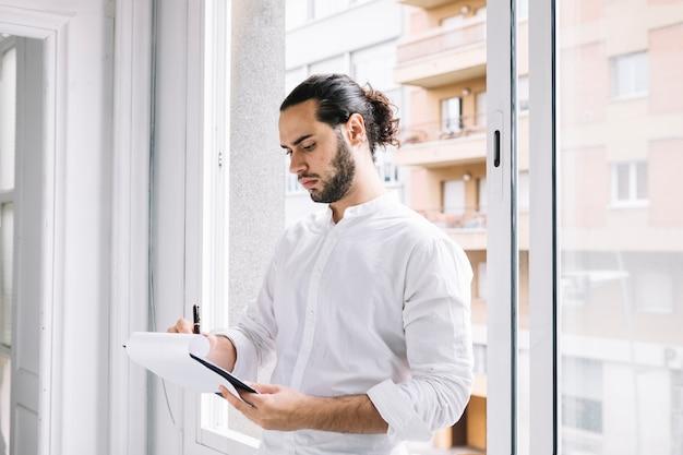 Jeune Homme Debout Près De La Fenêtre En écrivant Sur Le Bloc-notes Avec Un Stylo Photo Premium