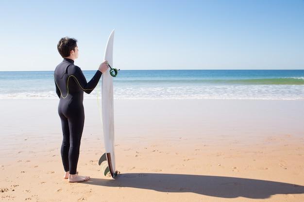 Jeune homme debout près de la planche de surf sur la plage d'été Photo gratuit