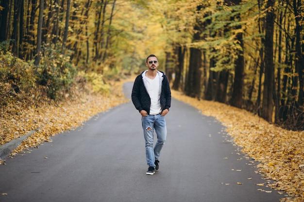 Jeune homme debout sur une route dans un parc en automne Photo gratuit