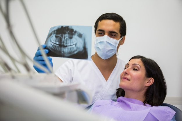 Jeune Homme Dentiste Examinant Les Rayons X Avec La Patiente Photo gratuit