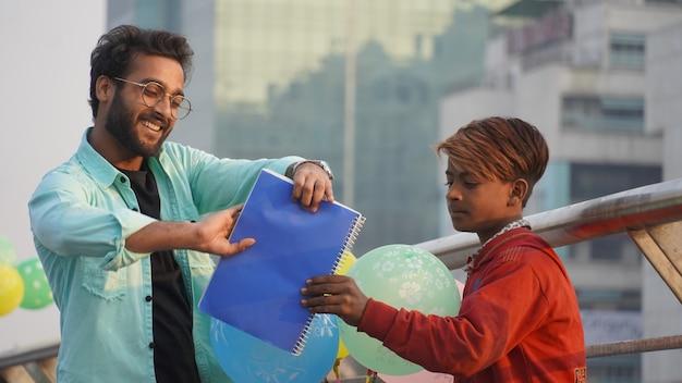 Jeune Homme Donnant Des Livres à Un Enfant Pauvre Pour étudier Photo Premium