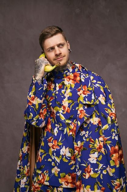 Jeune homme drôle en vêtements à fleurs utilisant une banane comme téléphone Photo gratuit