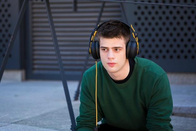 Jeune homme écoutant de la musique au casque Photo gratuit