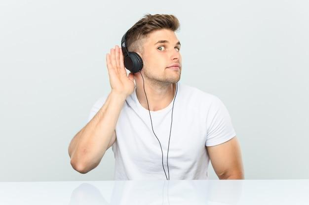Jeune homme écoutant de la musique avec des écouteurs essayant d'écouter un commérage. Photo Premium