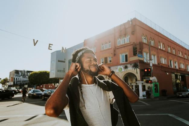 Jeune homme écoutant de la musique en marchant dans les rues Photo gratuit