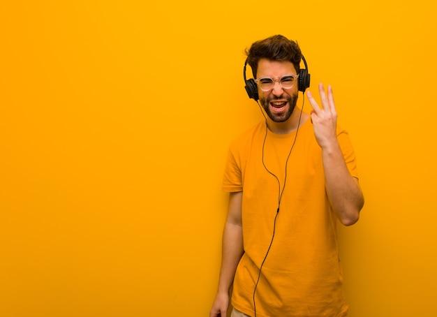 Jeune Homme écoutant De La Musique Montrant Le Numéro Trois Photo Premium