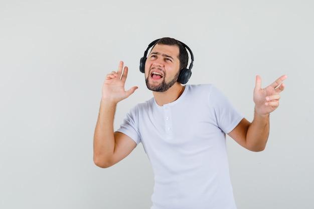 Jeune Homme écoutant De La Musique En T-shirt Blanc Et à La Recherche D'énergie. Vue De Face. Photo gratuit