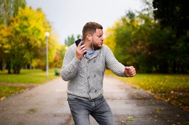 Jeune Homme Avec Des écouteurs Qui Dansent Sur Une Allée Dans Le Parc Photo gratuit
