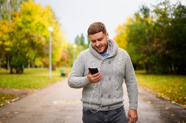 Jeune homme avec des écouteurs en regardant smartphone Photo gratuit