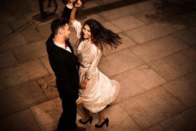Jeune homme élégant, tenant la main de femme gaie attrayante tourbillonnante Photo gratuit