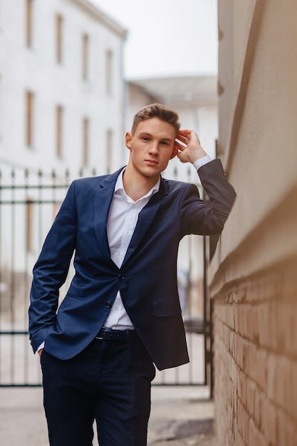 Jeune Homme élégant Avec Un Visage Monumental Se Promène Dans Une Ville Cool Près Des Murs En Bois Et En Pierre Photo Premium