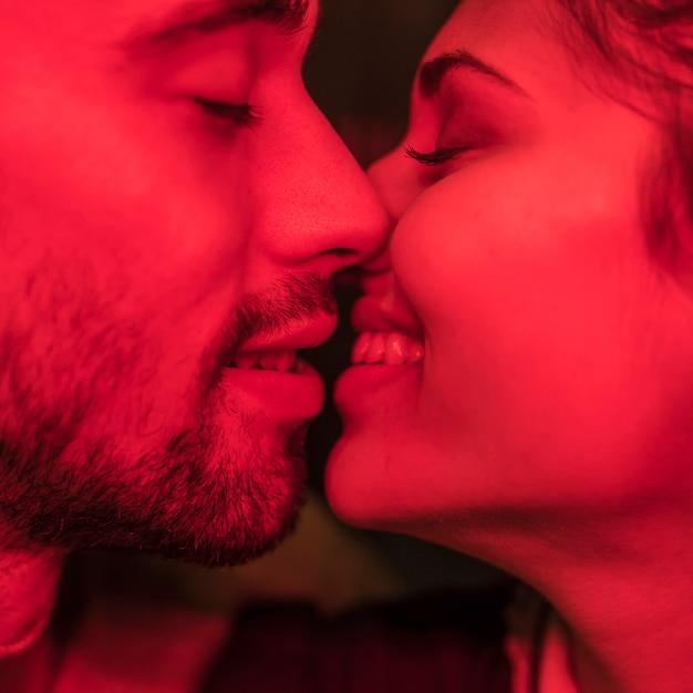 Jeune homme embrasse une femme souriante Photo gratuit