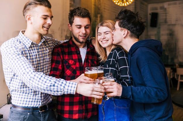 Jeune homme embrasse sa copine tout en grillant les verres de bière avec un ami Photo gratuit